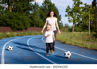 Mother and son in white T-shirts at the stadium.Blue coating on the stadium track and soccer balls.A mother plays with a child on a walk.Mom catches up with her son during the game.The child runs away - Shutterstock ID 2023361225