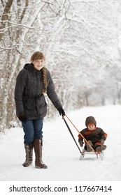 mother with son in winter park with sled