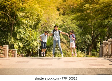 Mother and sons jumping together in the park summer time