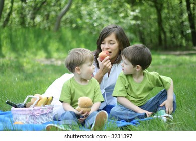 mother and sons relaxing - family picnic in the forest
