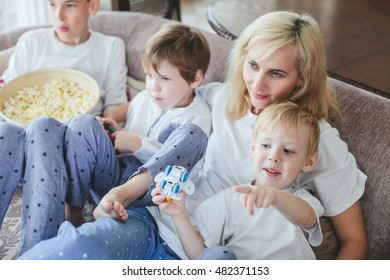 mother and sons are sitting on the couch watching television with popcorn in the kitchen