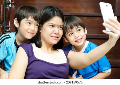 Mother and sons taking selfie with mobile in house