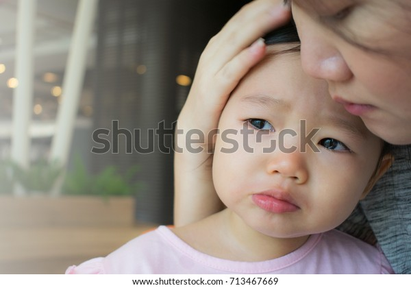 Mother soothing crying little girl.