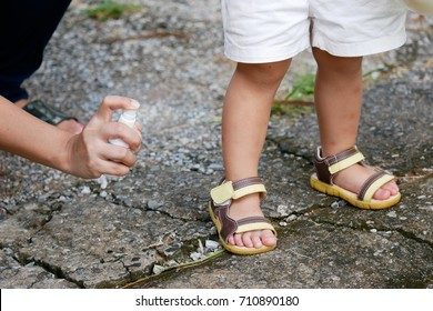 Mother spraying insect or mosquito repellents on skin girl, mosquito repellent for babies, toddlers that will protect your children from mosquitoes and other insects.