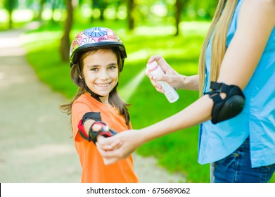 Mother spraying insect repellents on skin girl