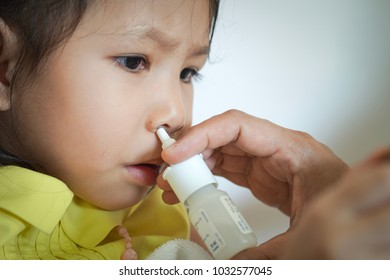 Mother is spraying sinus treatment for daughter.