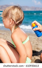 Mother spraying sunblock on her  daughter's back before sunbathing on a beach