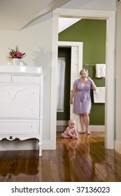 Mother standing beside chubby baby sitting on wood floor