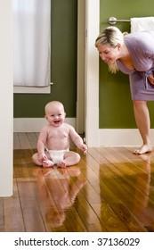 Mother standing beside happy baby sitting on wood floor