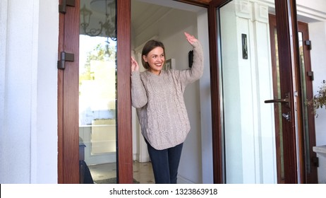 Mother standing by door and waving hand to children walking to school, goodbye