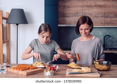 Mother standing by the table at home and serving french fries with chicken nuggets for a lunch