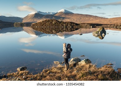 A mother standing on lakeside holding baby in her arms as both glance at Loch Etive where a mountain range partially covered in snow is reflected on the calm lake's calm water under a blue sky