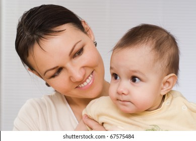 mother stands and holds the baby
