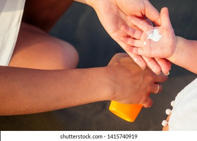 mother in stylish glasses and white dress is putting orange spray bottle SPF on newborn baby one year old daughter a sunscreen on the beach