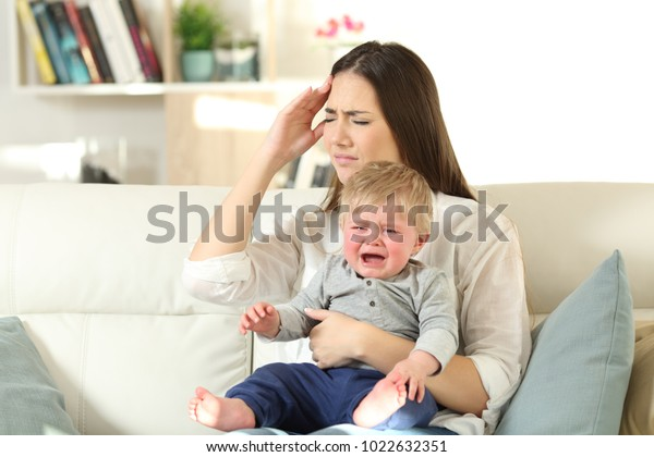 Mother suffering and baby crying desperately sitting on a couch in the living room at home