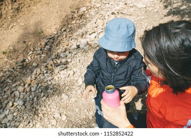 mother suggesting son to drink water from bottle