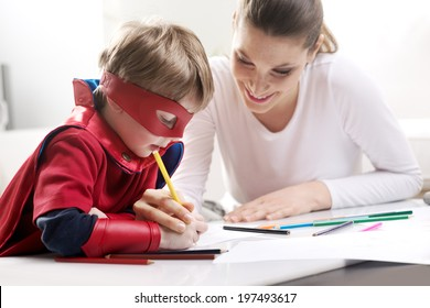 Mother and superhero child playing and drawing together in the living room.