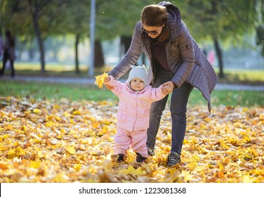 Mother supporting baby daughter and helping her make first steps. Mom and daughter on walk in autumn park.