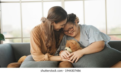 Mother supporting sweet down syndrome daughter to learn and relax from the internet, embracing child to encourage down syndrome girl at home.