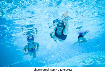 mother swimming and diving in the swimming pool with children