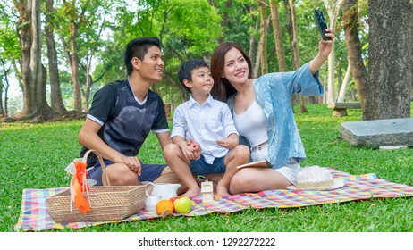 mother take selfie photo with camera phone with father and kid in park.Happy family picnic concept.