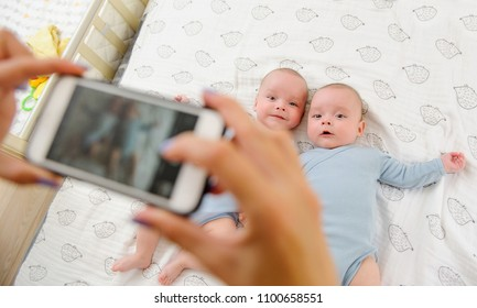 Mother takes a photo of her cute children in bed, view from above. Family memories