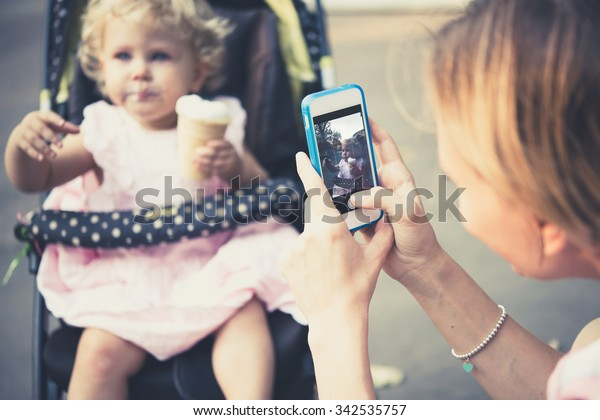 Mother takes a photo of her daughter eating ice-cream during a walk outdoors. Toned image