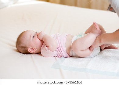 Mother taking care of infant baby and changing diaper