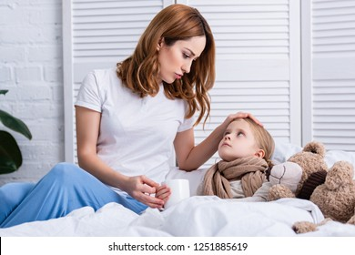 mother taking care of sick daughter in bedroom and giving her cup of tea, looking at each other