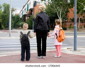 mother is taking children across the street