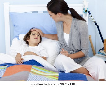 Mother taking her son's temperature lying in bed