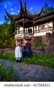 Mother taking a picture of her daughter in the front yard of the Chinese scholar garden which is a public park in staten island NY.
