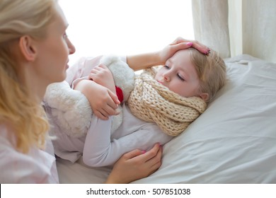 Mother taking the temperature of sick daughter