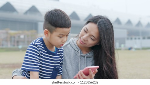 Mother talk to her son and use of smart phone together