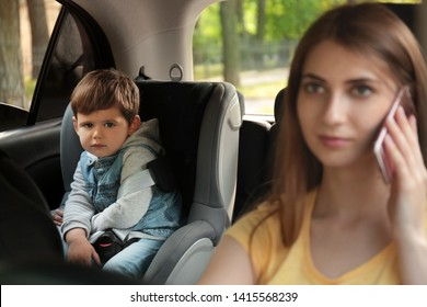 Mother talking by phone while driving car with her son on backseat. Child in danger