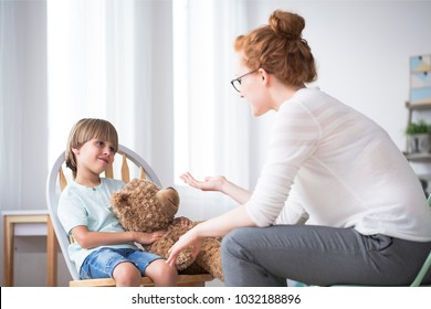 Mother talking to her polite, young son hugging a teddy bear