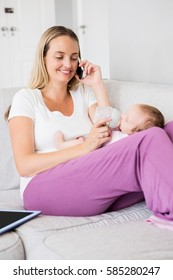 Mother talking on mobile phone while feeding her baby with milk bottle at home