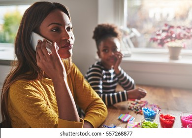 Mother talking on phone forgetting child that sits staring in background