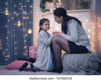 Mother talks to daughter. Cozy room in the house, festive atmosphere of Christmas