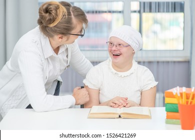 Mother talks with girl with Down Syndrome at home