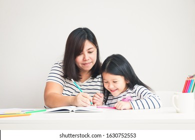 Mother taught homework to the little daughter sitting at the white table in the room. The concept of education for elementary school children
