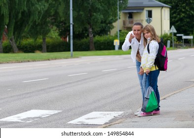 Mother teach daughter about safety rules before crossing the street on the school way