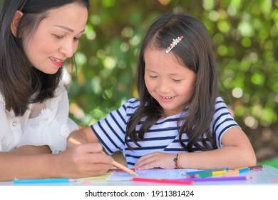 mother teach daughter asian children doing school homework in the home garden or park ,Home school concept