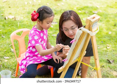 Mother teach daughter painting with easel in garden