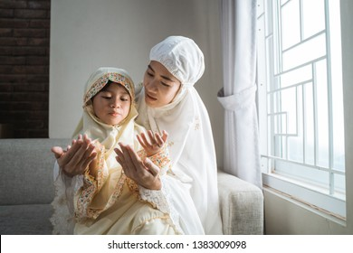 mother teach her daughter to pray with her hand open palm
