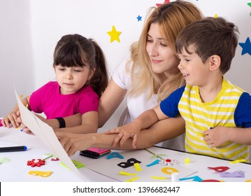 Mother or teacher learning english letters with children. Parent learning and playing with kids. Homeschooling