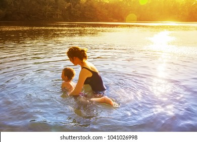 mother teaches a child to swim outdoors. little boy learning to swim. the concept of swim lesson and family recreation