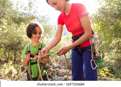 The mother teaches the child to tie a safety knot for climbing, Protective equipment for climbing and sports tourism, A boy learns to knit the safety knot from the rope, Climbing rope for belaying.