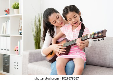 Mother teaches daughter how to play the guitar and little Asian girl also deal the vocal part of the performance. They are practicing their talent shoe in the living room.