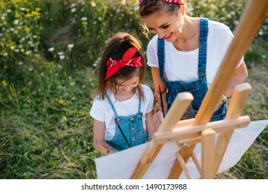 mother teaches daughter paint in park. Sunny nature, mom and daughter paint a picture in a park , painting a Little Child, Child Creativity. Mother's Day